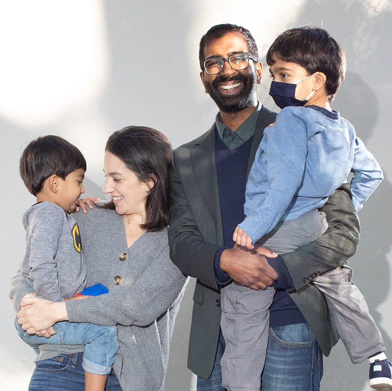 Shekar Krishnan and his wife Zoe Levine holding their two young boys